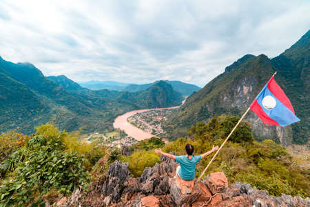 Woman with arms outstretched conquering mountain top at Nong Khiaw Nam Ou River valley Laos mature people traveling millenials concept travel destination in South East Asia