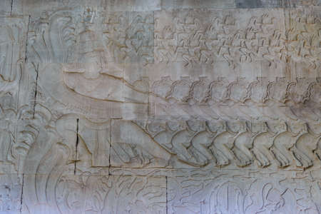 Famous bas reflief carved in the wall of Angkor Wat temple, most visited tourist site, Cambodia. Details, close up of epic battles rock carving.