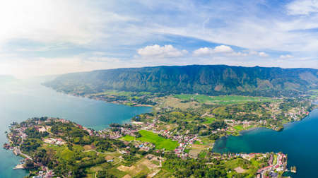 Aerial: lake Toba and Samosir Island view from above Sumatra Indonesia. Huge volcanic caldera covered by water, traditional Batak villages, green rice paddies, equatorial forest. 写真素材