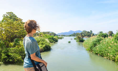 Woman looking at the Mekong River on the 4000 islands Laos daytime, famous travel destination backpacker in South East Asia Banco de Imagens