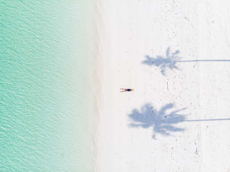 Aerial top down view tropical beach caribbean sea. Woman sunbathing between palm tree shade on white sand beach turquoise water. Travel exotic vacation. Imagens
