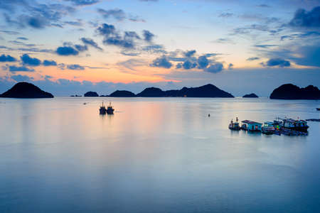 Vietnam Cat Ba bay at sunset with floating fishing boats on sea, cloudscape tropical weather, colorful sky and islands profile at the horizon. Long exposure