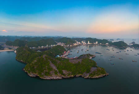 Aerial unique view Vietnam Cat Ba bay with floating fishing boats on sea, cloudscape tropical weather inspirational sunset, epic city skyline and skyscraper, scenic green mountain. Reklamní fotografie