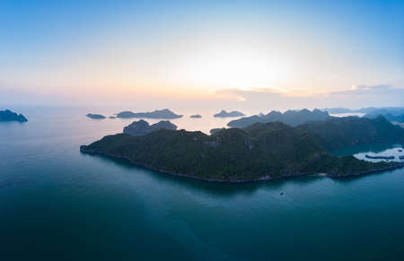 Aerial view Cat Ba bay Vietnam epic sunset reflection on sea, colorful sky and islands profile at the horizon, popular tourist destination, unique seascape