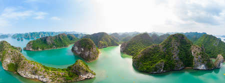 Aerial view of Ha Long Bay Cat Ba island, unique limestone rock islands and karst formation peaks in the sea, famous tourism destination in Vietnam. Scenic blue sky.