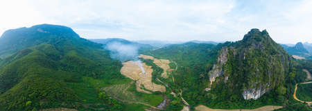 Aerial panoramic Muang Ngoi Laos river valley yellow ripe rice fields agriculture dramatic landscape scenic pinnacle cliff mountain range famous travel destination in South East Asia