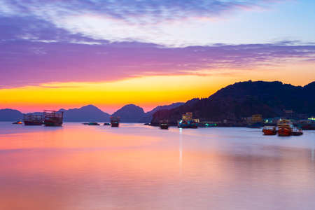 Unique sunset sky in Vietnam Cat Ba bay with floating fishing boat village on sea, cloudscape tropical weather, long exposure blurred motion.