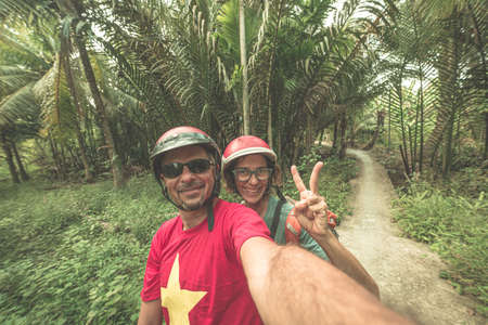 Couple taking selfie on motorbike. Man and woman with helmet biking in the Mekong Delta region, South Vietnam. Lush green coconut palm tree woodland and water channel. Toned. Zdjęcie Seryjne