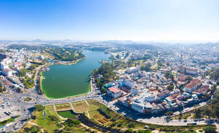 Aerial view of Da Lat city beautiful tourism destination in central highlands Vietnam. Clear blue sky. Urban development texture, green parks and city lake.