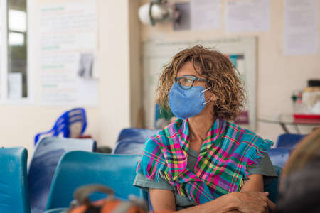 Caucasian woman wearing sanitary mask indoors while traveling in Vietnam. Tourist in waiting room with medical mask protection against risk of  virus epidemy in Asia