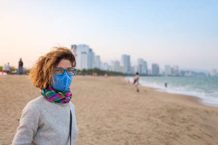 Caucasian woman wearing sanitary mask outdoors in Nha Trang beach, famous travel detination in Vietnam. Tourist with medical mask protection against risk of virus epidemy in Asia Фото со стока