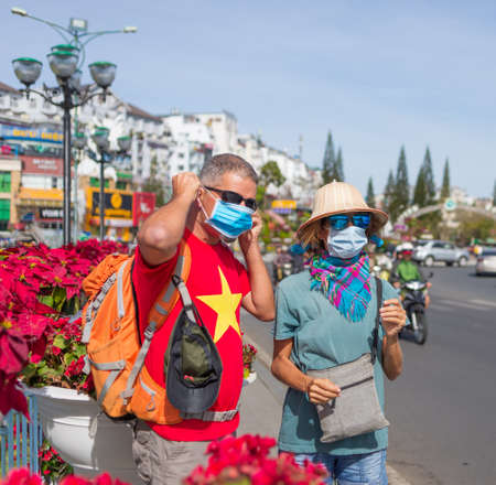 Caucasian woman and man wearing sanitary mask outdoors in Da Lat city centre Vietnam. Tourist couple with medical mask protection against risk of flu virus epidemy in Asia. Anti smog mask traffic pollution.