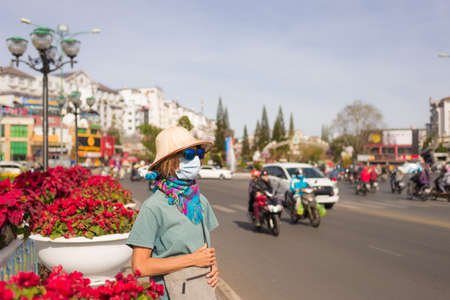 Caucasian woman wearing sanitary mask outdoors in Da Lat city centre Vietnam. Tourist with medical mask protection. Anti smog mask traffic pollution. Vietnam Editorial