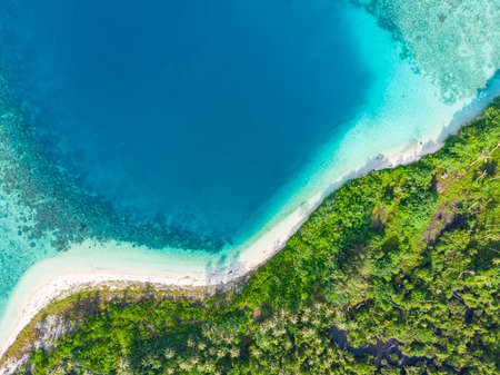 Aerial top down view tropical paradise pristine beach rainforest blue lagoon bay coral reef caribbean sea turquoise water at Banyak Islands Indonesia Sumatra remote travel adventure away from it all