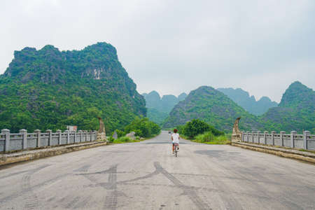 Woman riding bicycle alone on the road in scenic landscape among rock pinnacles and green valleys. Unique view of Trang An Ninh Binh, Vietnam. Social distancing, lone traveling, alternative mobility.