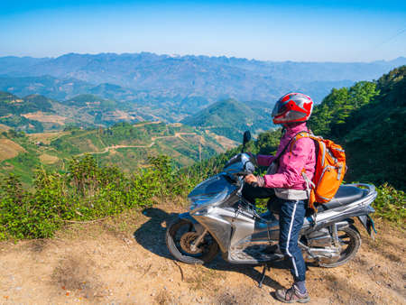 One person riding bike on Ha Giang motorbike loop, famous travel destination bikers easy riders. Ha Giang karst geopark mountain landscape in North Vietnam. Winding road in stunning scenery.  Stok Fotoğraf