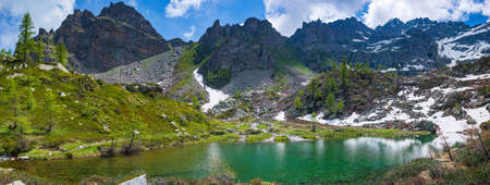 Alpine lake in idyllic environment amid rocks and forest. Natural reservoir of fresh water at high altitude on the mountains.
