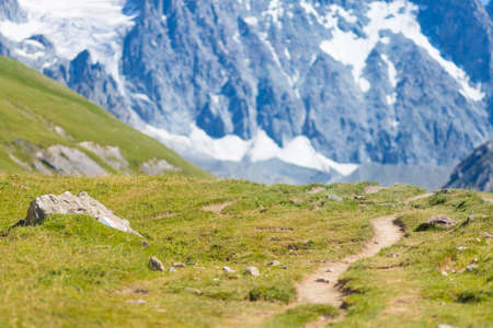 Mountain trail on the french Alps, Massif des Ecrins. Scenic alpine landscape at high altitude with glacier, green meadows and hiking paths for tourism summer vacation