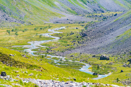 Alpine stream in idyllic valley amid rocks and green meadows, Natural reservoir of fresh water at high altitude on the mountains. Фото со стока
