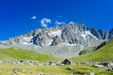 Mountain landscape on the french Alps, Massif des Ecrins. Scenic rocky mountains at high altitude with glacier, green meadows and hiking paths for tourism summer vacation Фото со стока