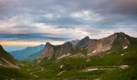 Mountain landscape on the Alps, rocky mountains at high altitude, moody sky green valley and hiking paths for tourism summer vacation