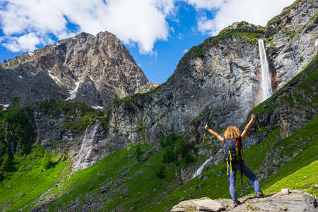 Lady hiker looking at waterfall on mountain. One person with backpack outdoor activity in scenic alpine landscape, summer vacation on the Alps, fitness wellbeing freedom