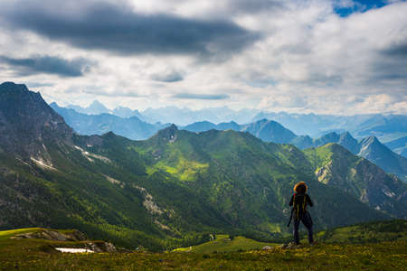 Woman with backpack resting on mountain top, looking at view dramatic landscape valley summer activity fitness wellbeing freedom concept, rear view