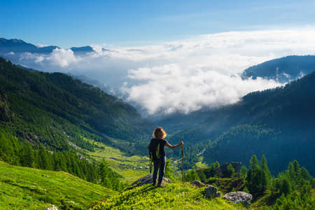 Woman resting on mountain top, looking at view dramatic landscape clouds over the valley, clear blue sky. Summer activity fitness wellbeing freedom success.
