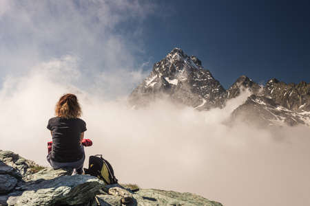 Woman resting on high mountain top, looking at view dramatic landscape majestic mountain peak over the clouds, clear blue sky. Summer activity fitness wellbeing freedom success. Фото со стока