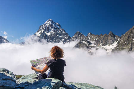 Woman on high mountain top, looking at map, view dramatic landscape majestic mountain peak over the clouds, clear blue sky. Summer activity fitness wellbeing freedom success. Фото со стока