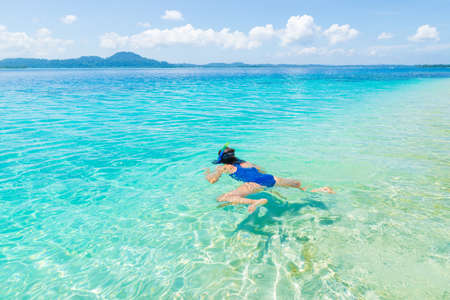 Woman snorkeling in caribbean sea, turquoise blue water, tropical island. Indonesia Banyak Islands Sumatra, tourist diving travel destination.