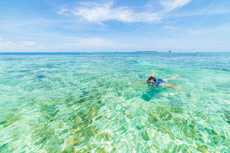 Woman snorkeling in caribbean on coral reef tropical turquoise blue water. Indonesia Wakatobi archipelago, marine national park, tourist diving travel destination Фото со стока