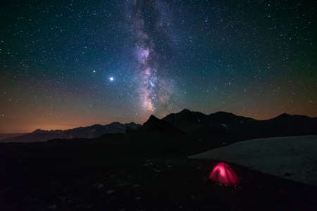 Milky way galaxy stars in the night sky over the Alps, illuminated camping tent in the foreground, snowcapped mountain range, photography stargazing Фото со стока