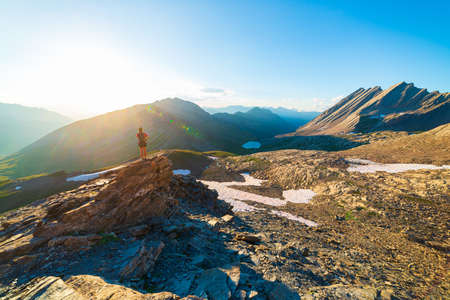 Woman hiker looking at view from mountain top against sun burst. One person hiking on vacation in scenic alpine landscape, summer activities fitness wellbeing freedom Фото со стока