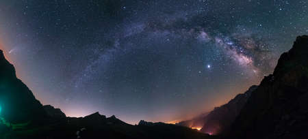Milky Way arc and stars in night sky over the Alps. Outstanding Comet Neowise glowing at the horizon on the left.