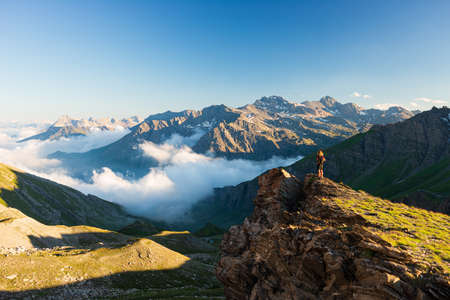 Woman success concept looking at view from mountain top, dramatic landscape clouds over the valley, sunset clear blue sky. Summer activity fitness wellbeing freedom loneliness. Фото со стока