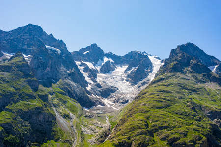 Mountain landscape on the french Alps, Massif des Ecrins. Scenic rocky mountains at high altitude with glacier Фото со стока
