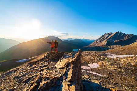 Couple of hikers looking at view from mountain top against sun burst. Man and woman on vacation in scenic alpine landscape, summer activities fitness wellbeing freedom