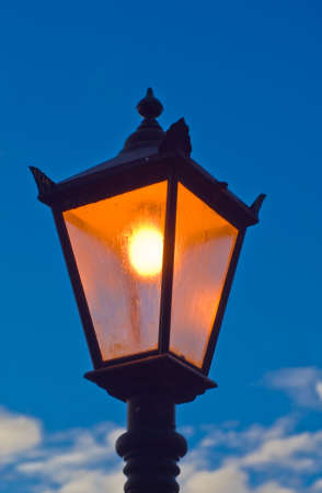 Lamppost glowing Orange against the blue sky with clouds