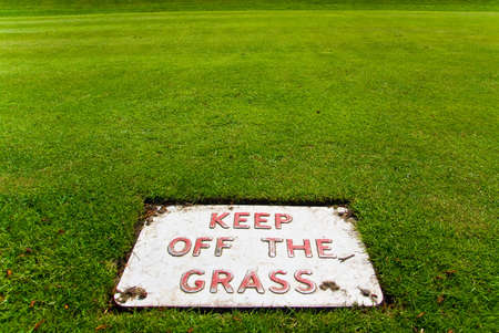 Keep off the grass sign on the grass itself Stock Photo