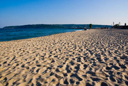 Sandy beach in Varna, Bulgaria, shot against the coastline and a bright blue sky Stock Photo