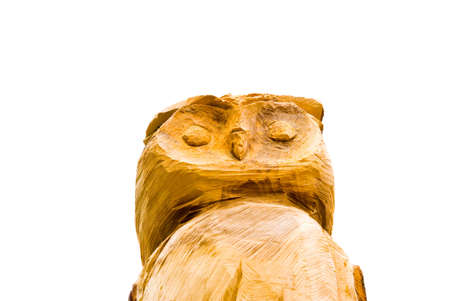 Wooden owl carved from a tree isolated on white photo