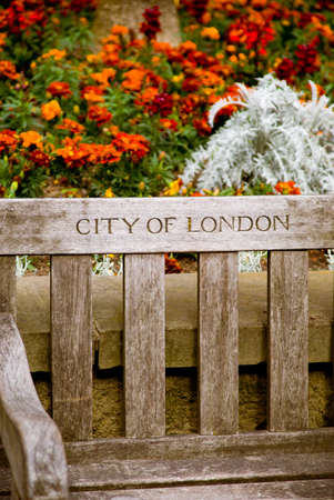 Old wooden bench in London against a flowers backgroud. Vintage look. Stock Photo
