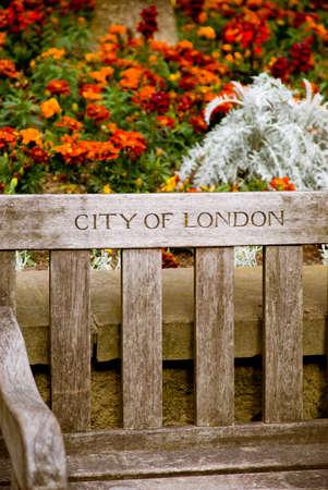 Vieux banc en bois � Londres contre un backgroud fleurs. Examiner mill�sim�s.  Banque d'images