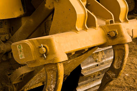 Excavator clamps and tracks covered in mud. Close up.