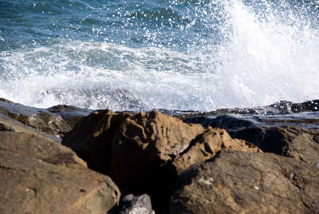 Wave crushing on rocks in Italy. Selective focus on the wave.