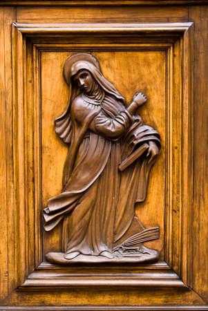 face centered: Virgin Mary carved in a wooden door in Florence, Italy. Stock Photo