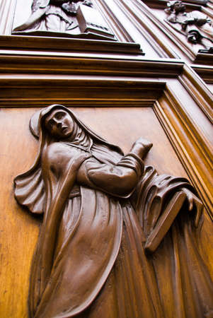 Virgin Mary carved in a wooden door in Florence, Italy. Stock Photo
