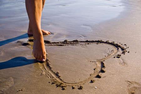 Dessiner une jeune fille de c?ur dans le sable.