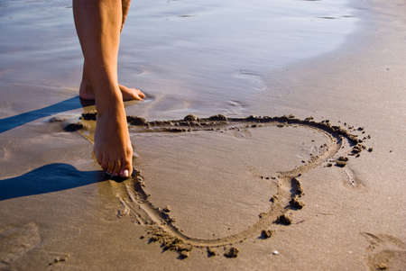 Girl drawing an heart in the sand.